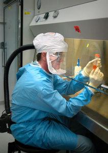 Investigador manipulando muestras del virus
